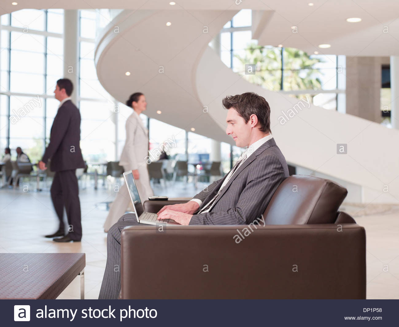 Businessman working in office waiting area - Stock Image