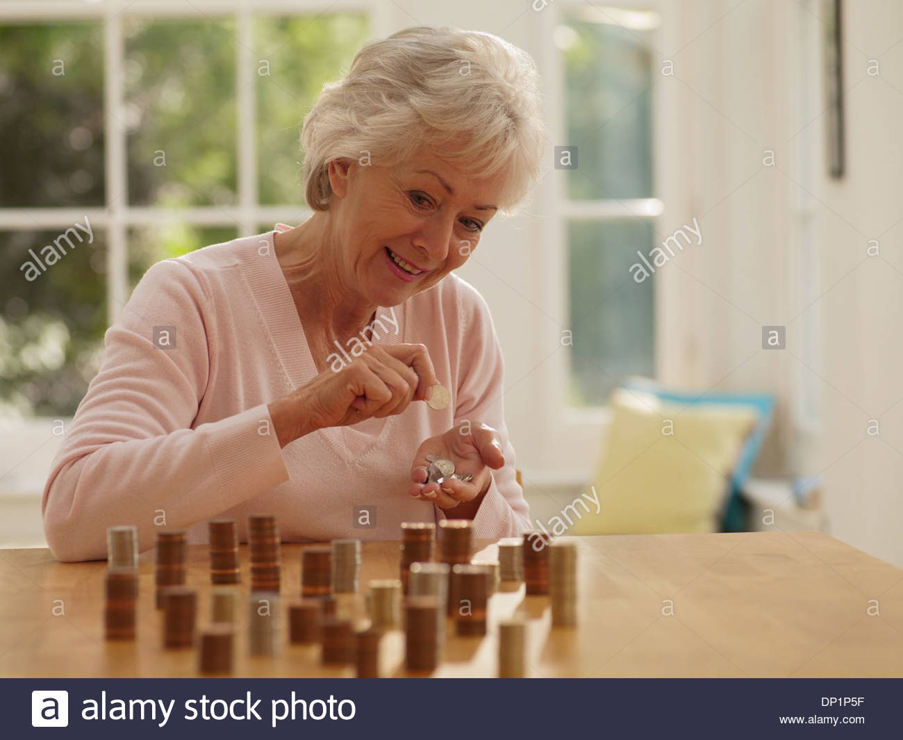 Woman putting coins into stacks - Stock Image