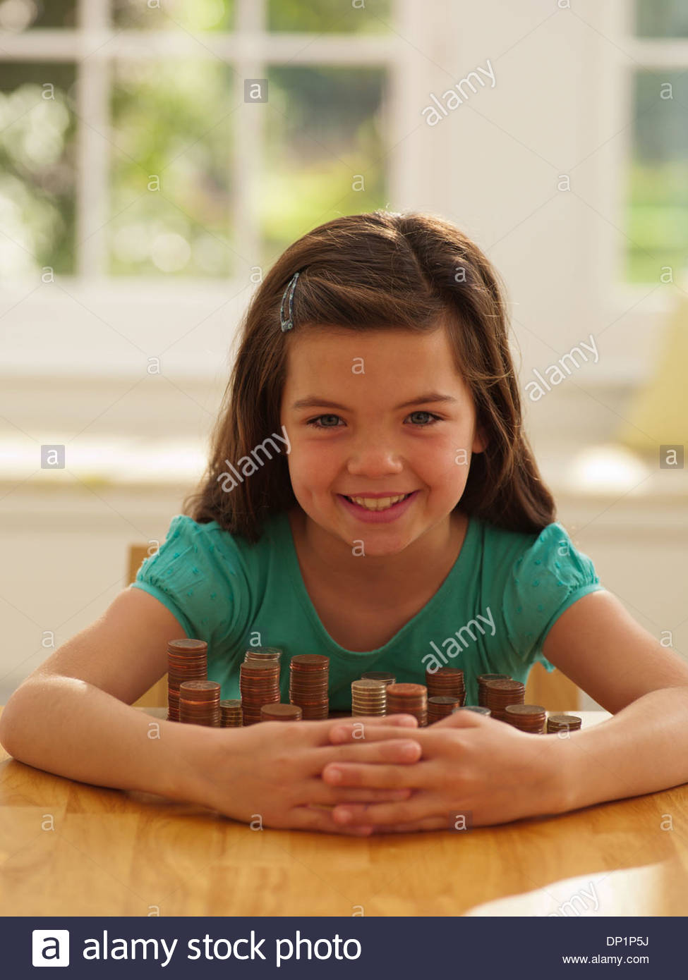 Smiling girl protecting stacks of coins - Stock Image