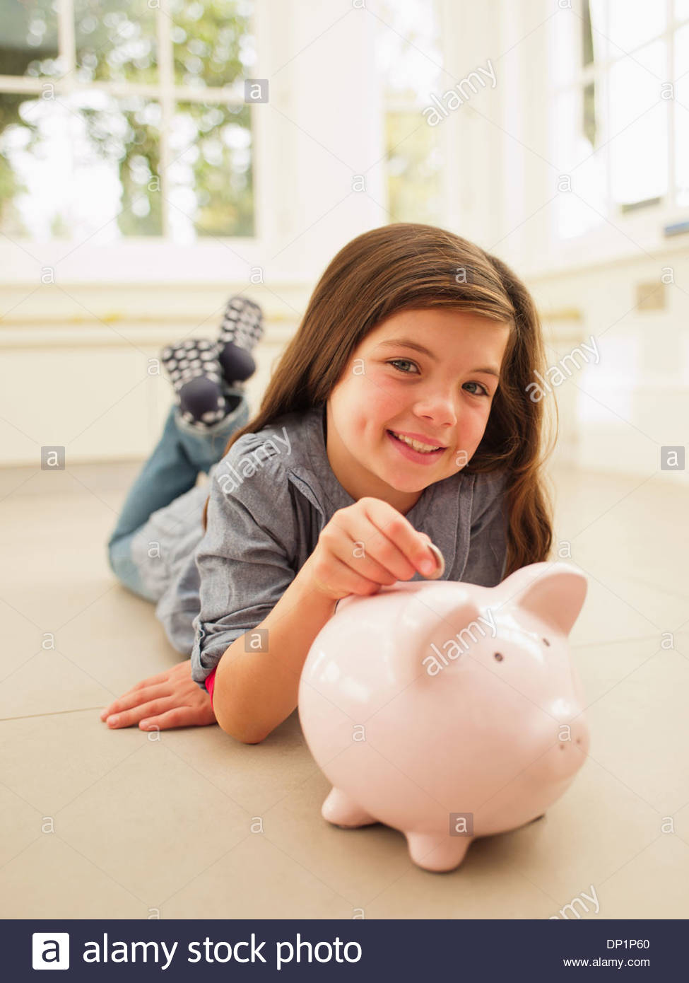 Girl putting coin into piggy bank - Stock Image