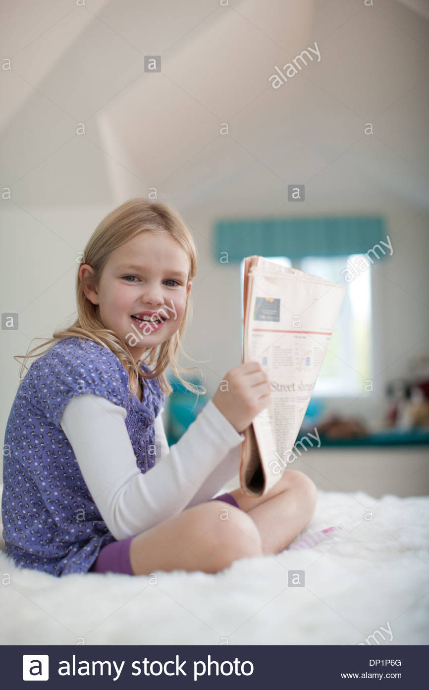 Girl sitting on bed reading newspaper - Stock Image