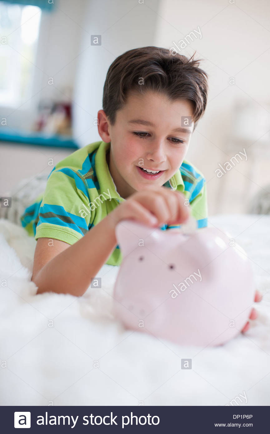 Boy laying in bed with piggy bank - Stock Image