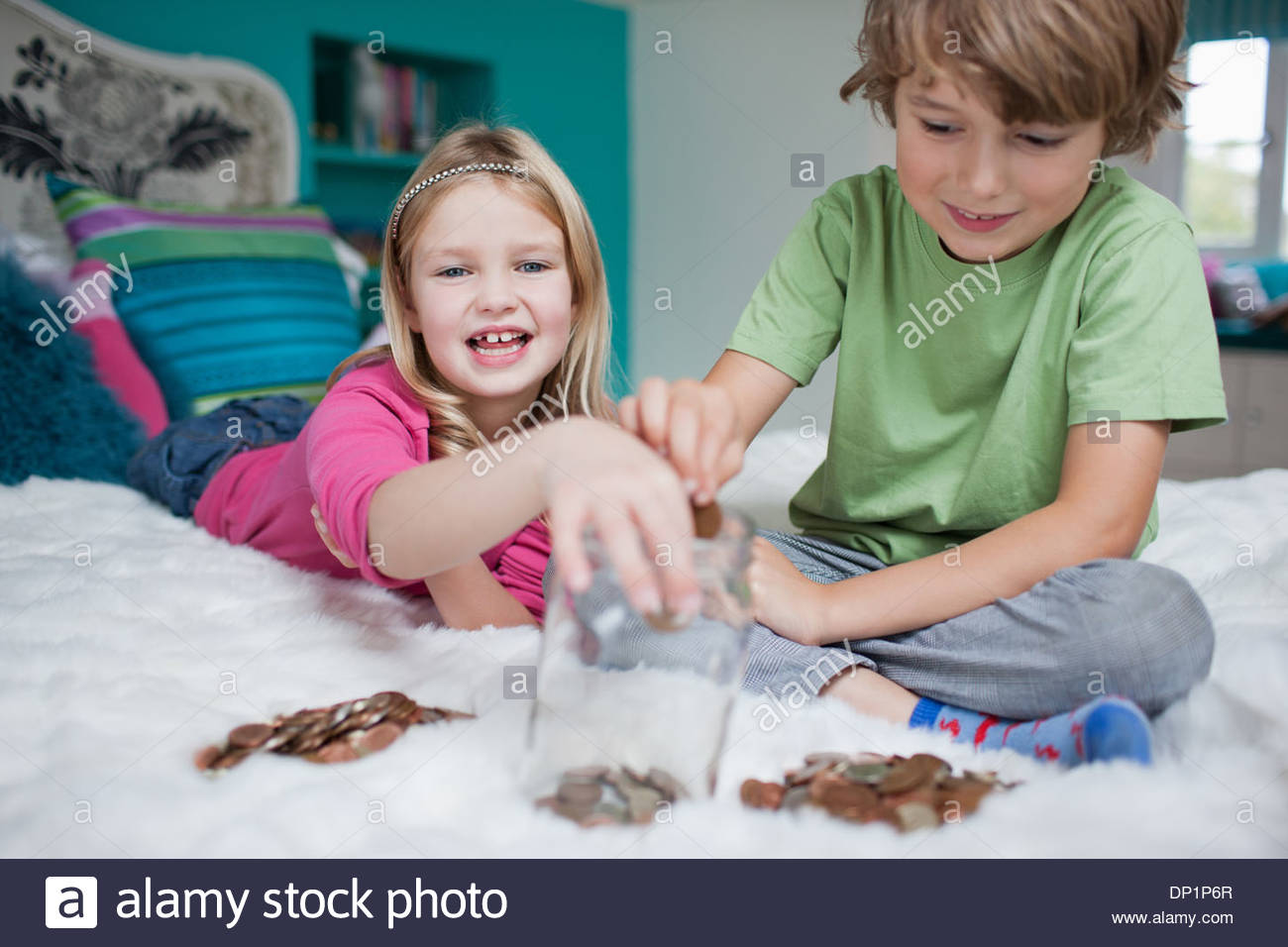 Brother and sister playing counting money in bedroom - Stock Image