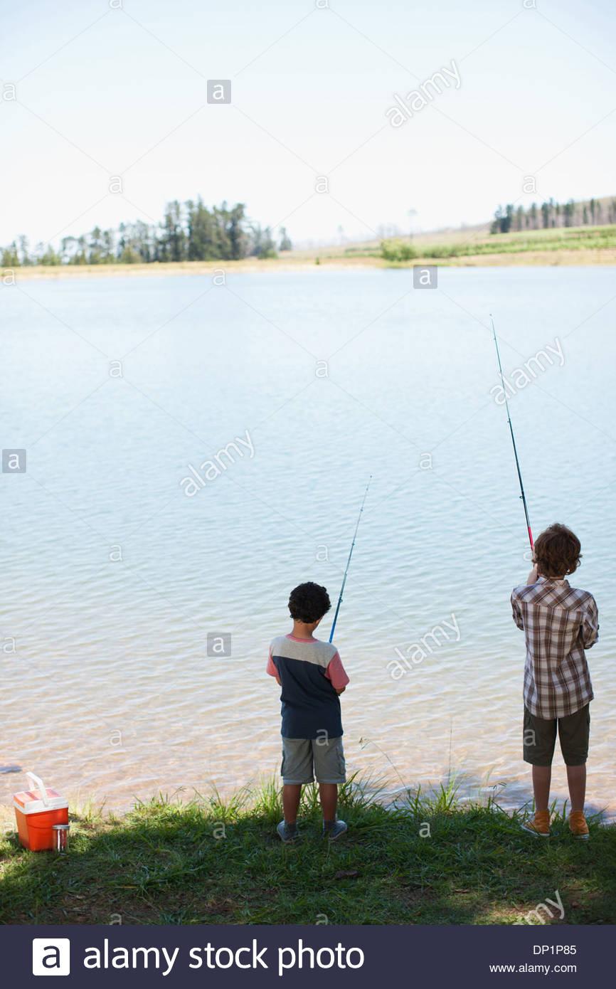 Brothers fishing lakeside - Stock Image
