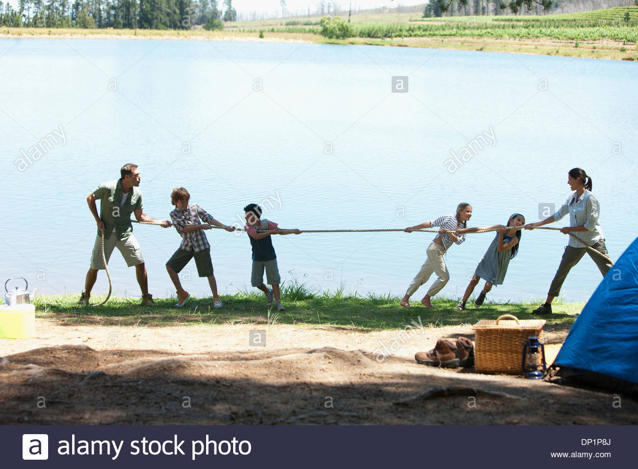 Family playing tug-of-war at campsite - Stock Image