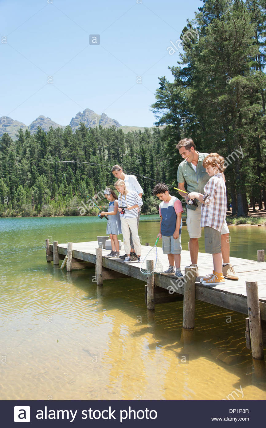 Family fishing off dock - Stock Image
