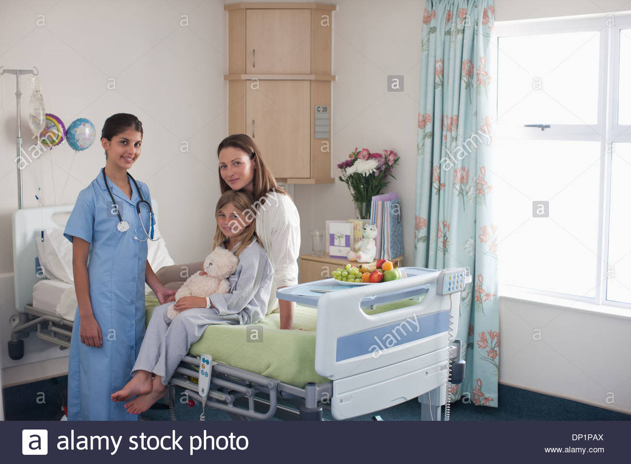 Nurse in childrenÂ's hospital with girl patient and mother - Stock Image