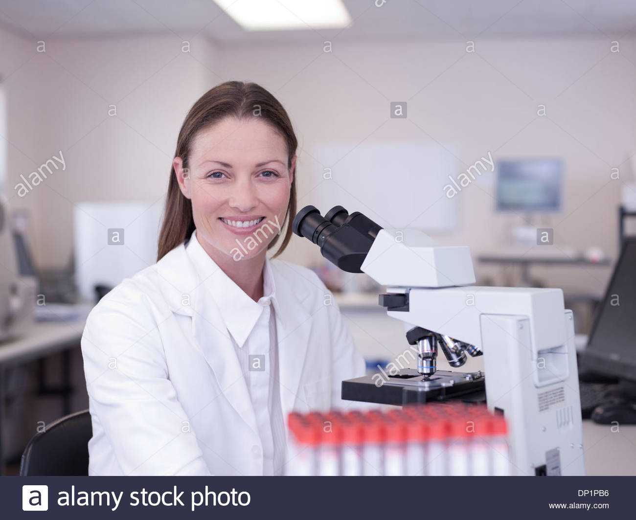 Portrait of scientist with microscope in laboratory - Stock Image