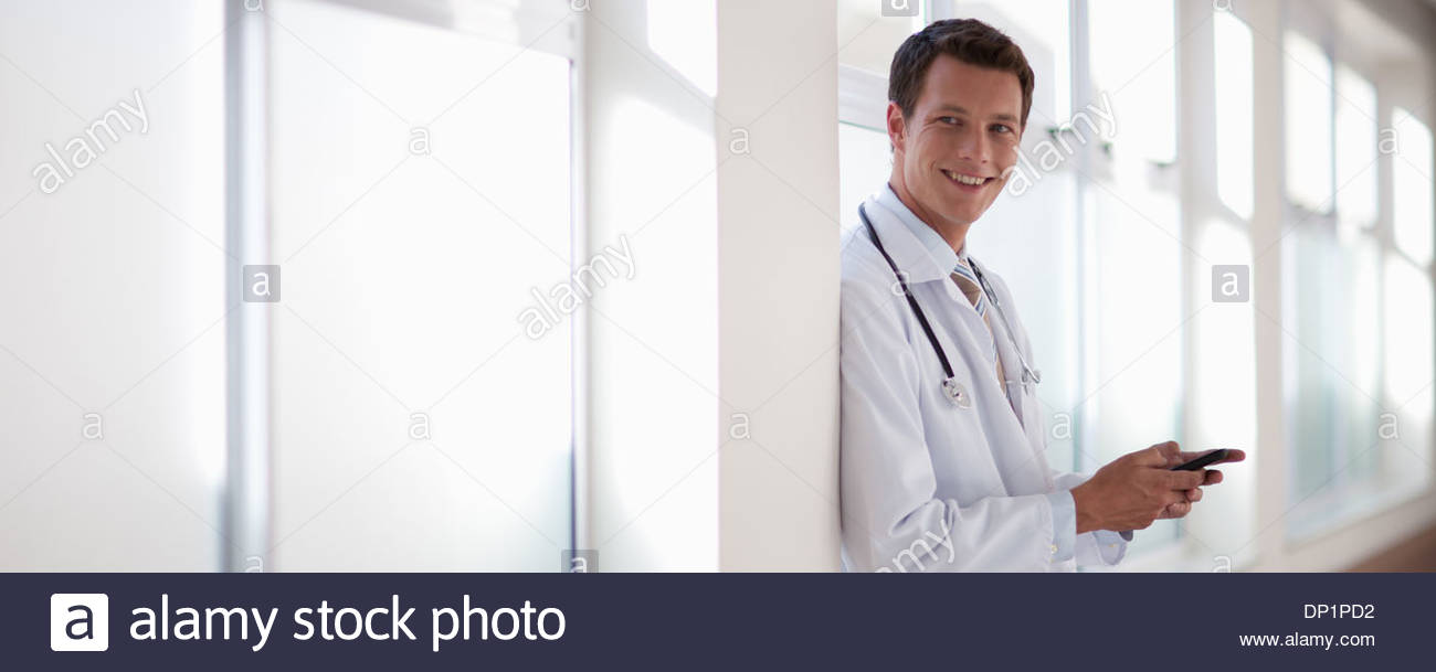 Doctor with cell phone in hospital corridor - Stock Image