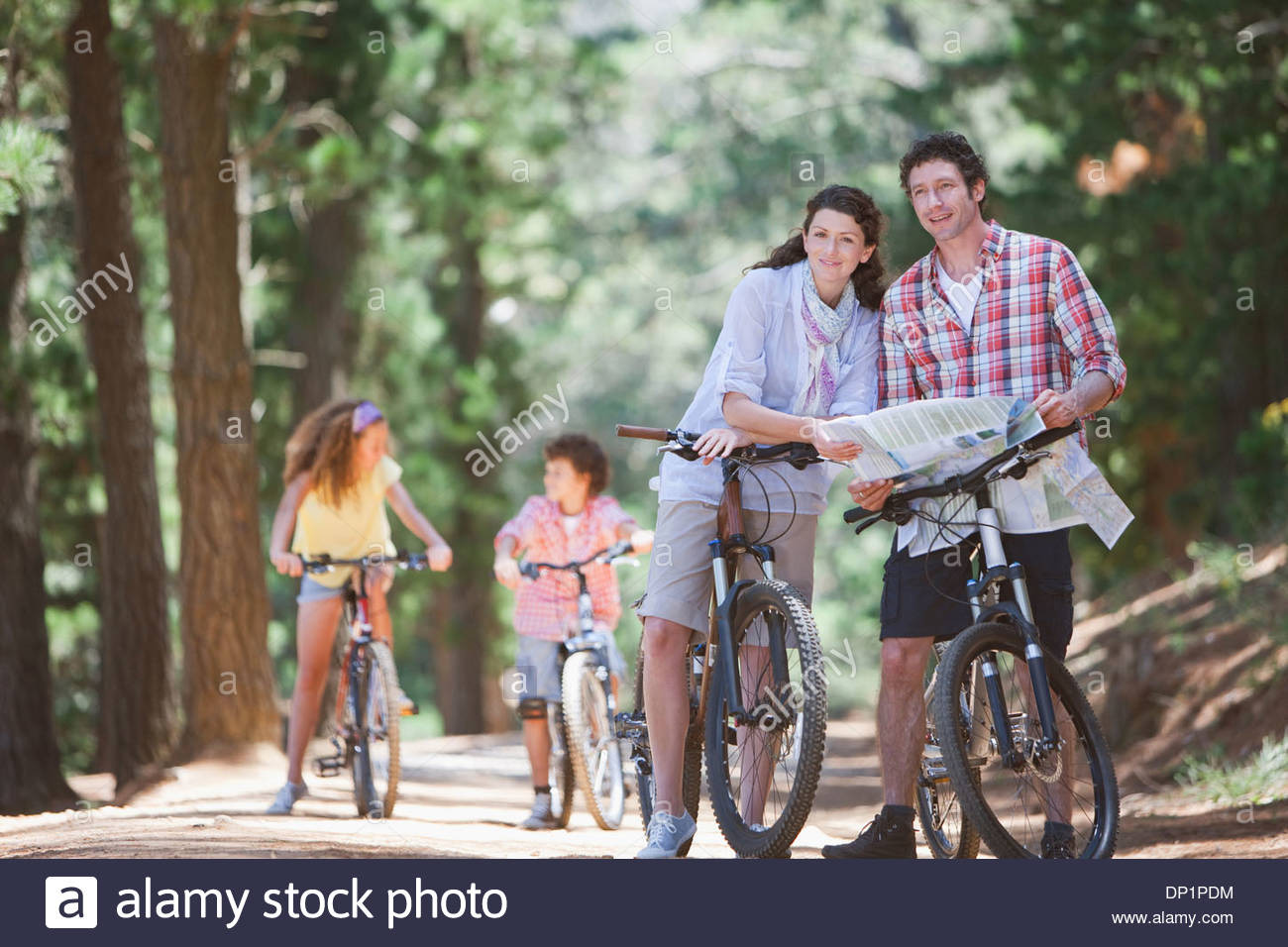 Family with bicycles looking at map in woods - Stock Image