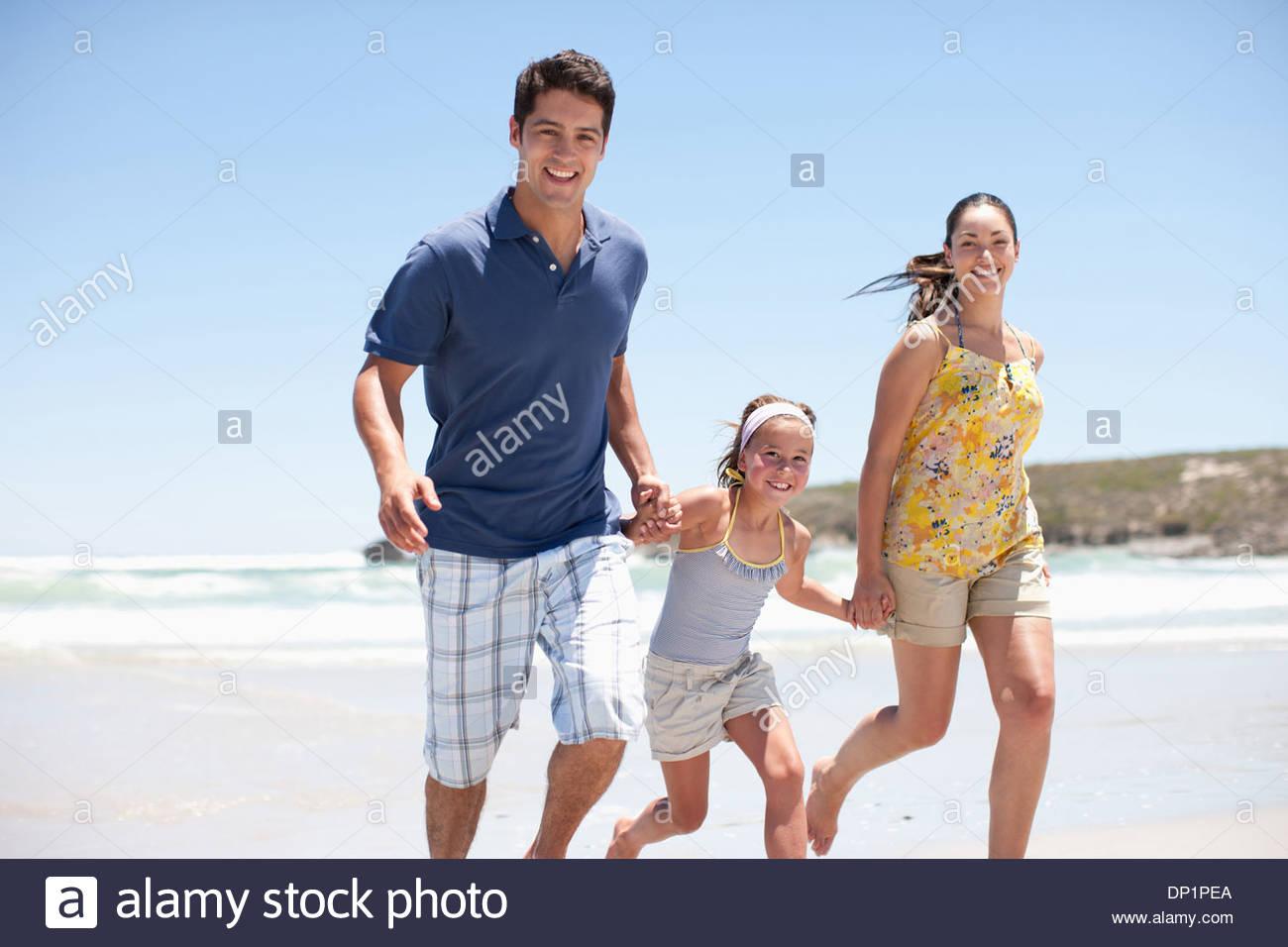 Family running on beach Stock Photo
