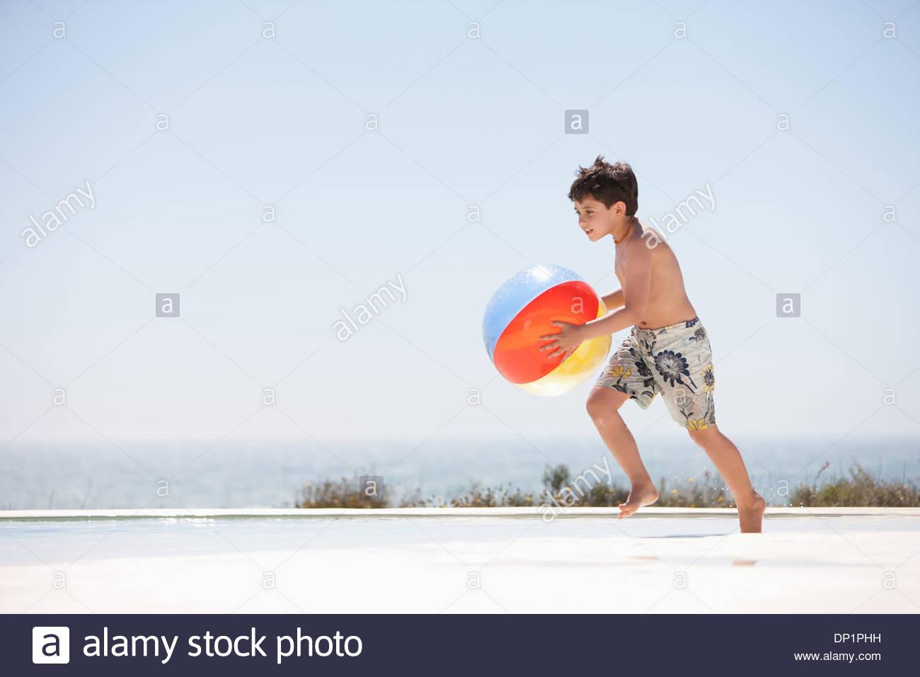 Boy holding beach ball beside pool - Stock Image