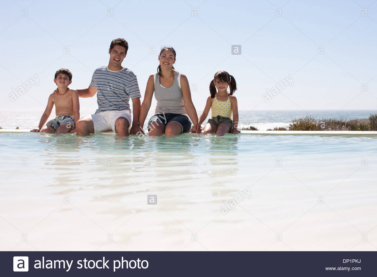 Family sitting with feet in infinity pool Stock Photo