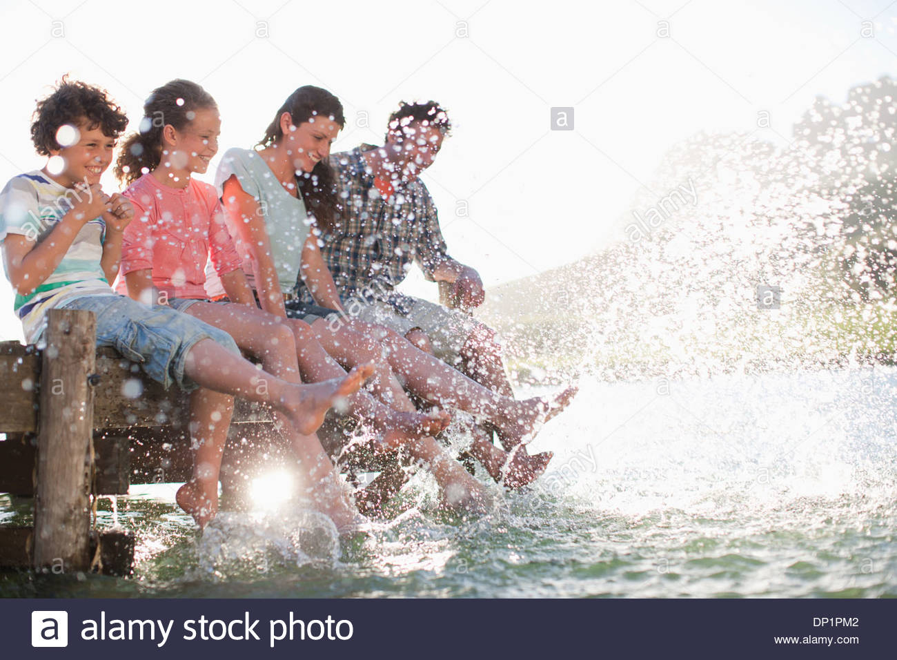 Family on dock splashing feet in lake - Stock Image