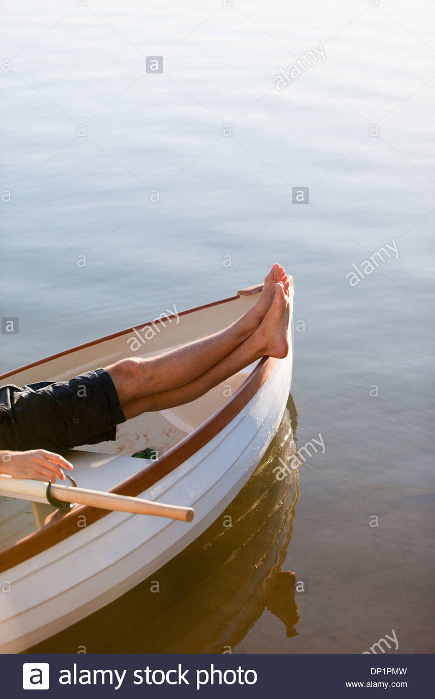 Bare feet in rowboat on lake - Stock Image