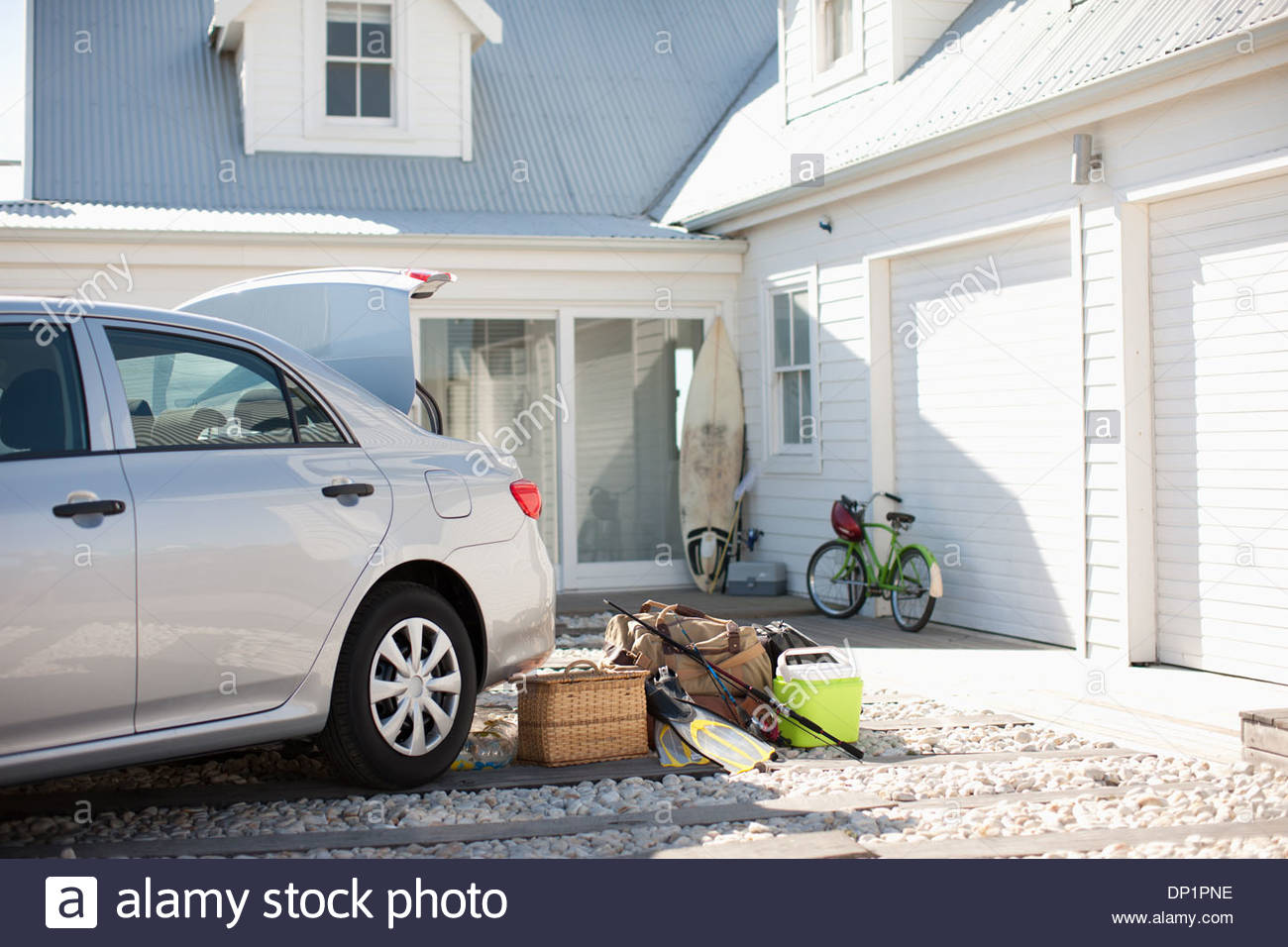 Picnic basket, fishing rod, flippers and bags outside car in driveway - Stock Image
