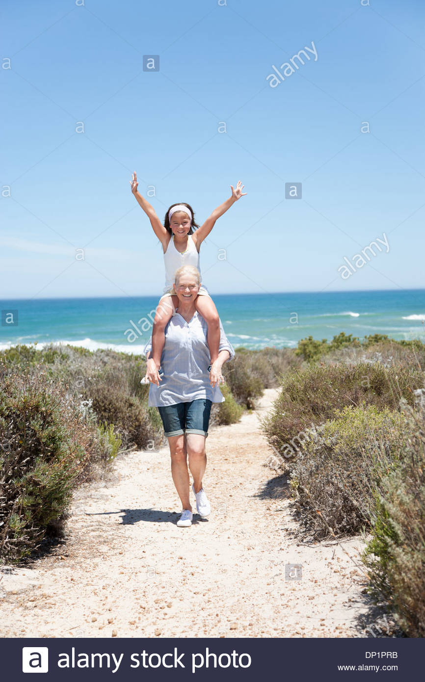 Grandmother carrying granddaughter on shoulders on beach - Stock Image