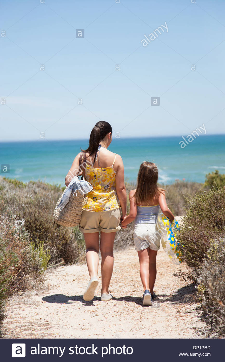 Mother and daughter walking on beach path - Stock Image