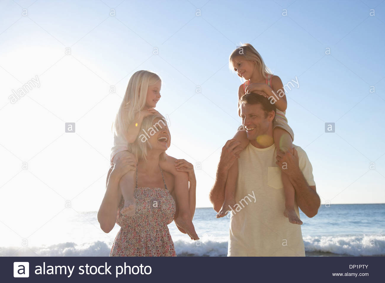 Parents carrying daughters on shoulders on beach Stock Photo