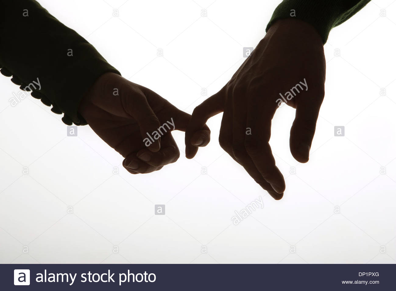 Hands linked by pinky fingers - Stock Image