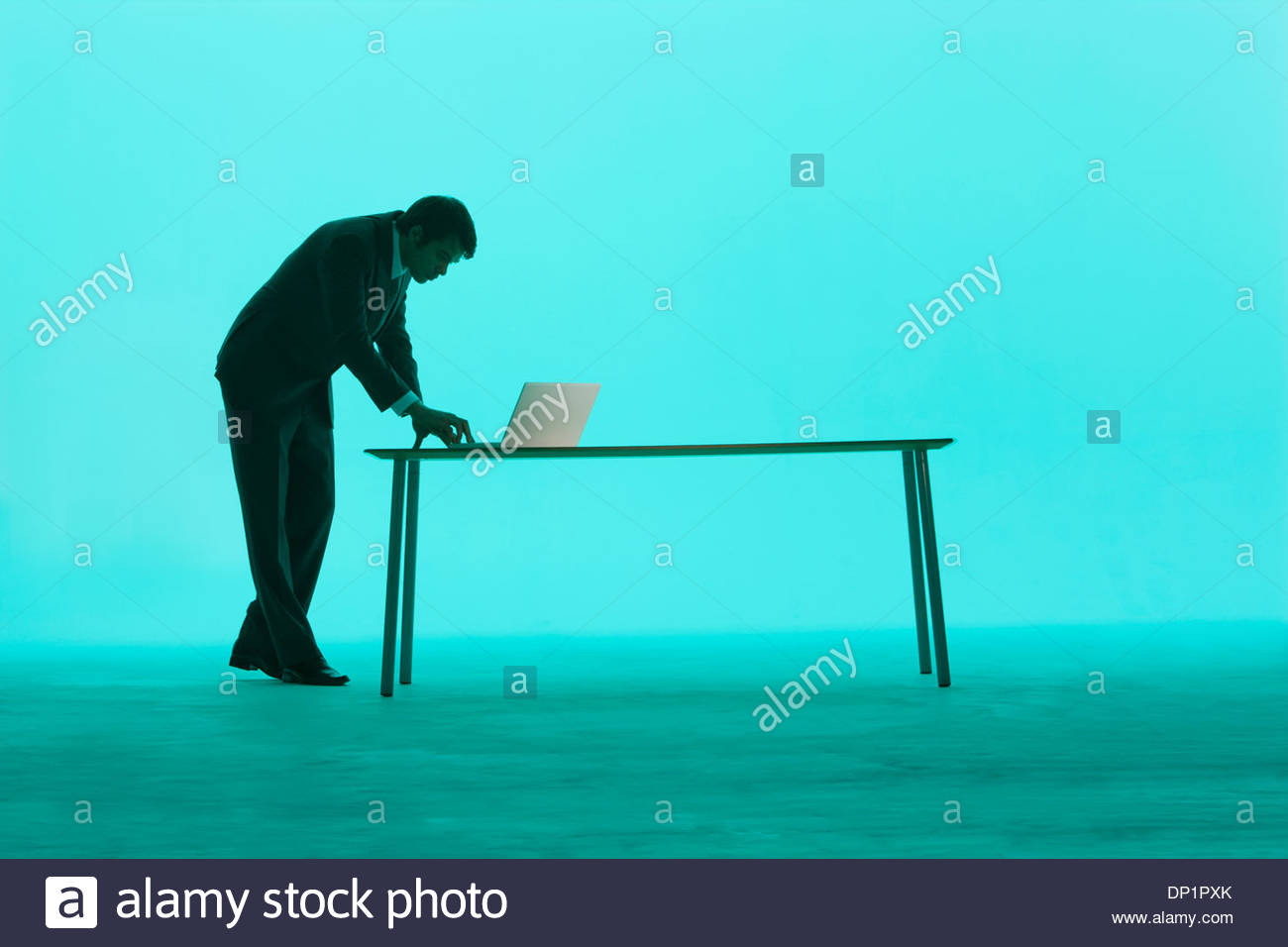 Businessman by a table using laptop - Stock Image