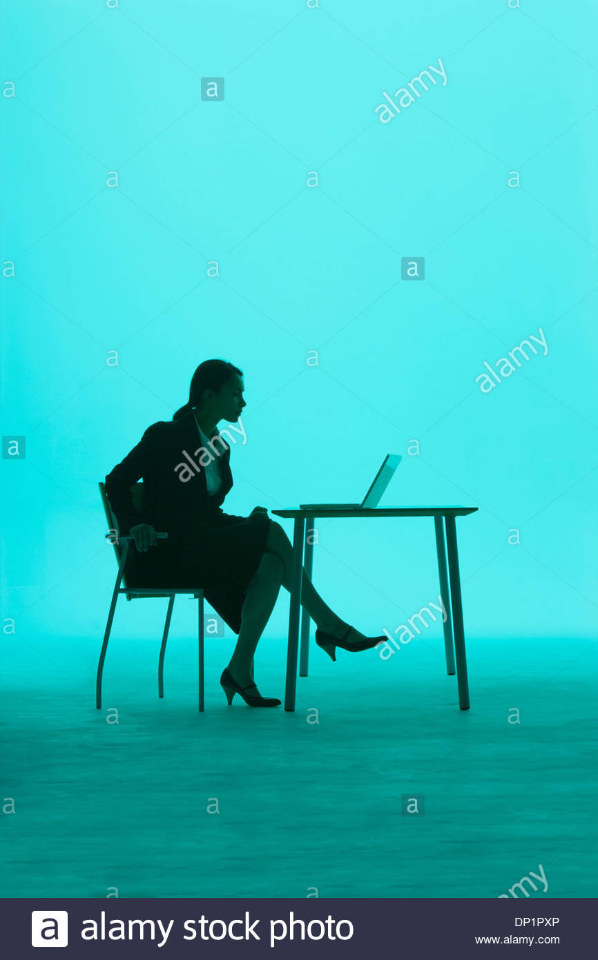 Businesswoman by a table with laptop on it - Stock Image