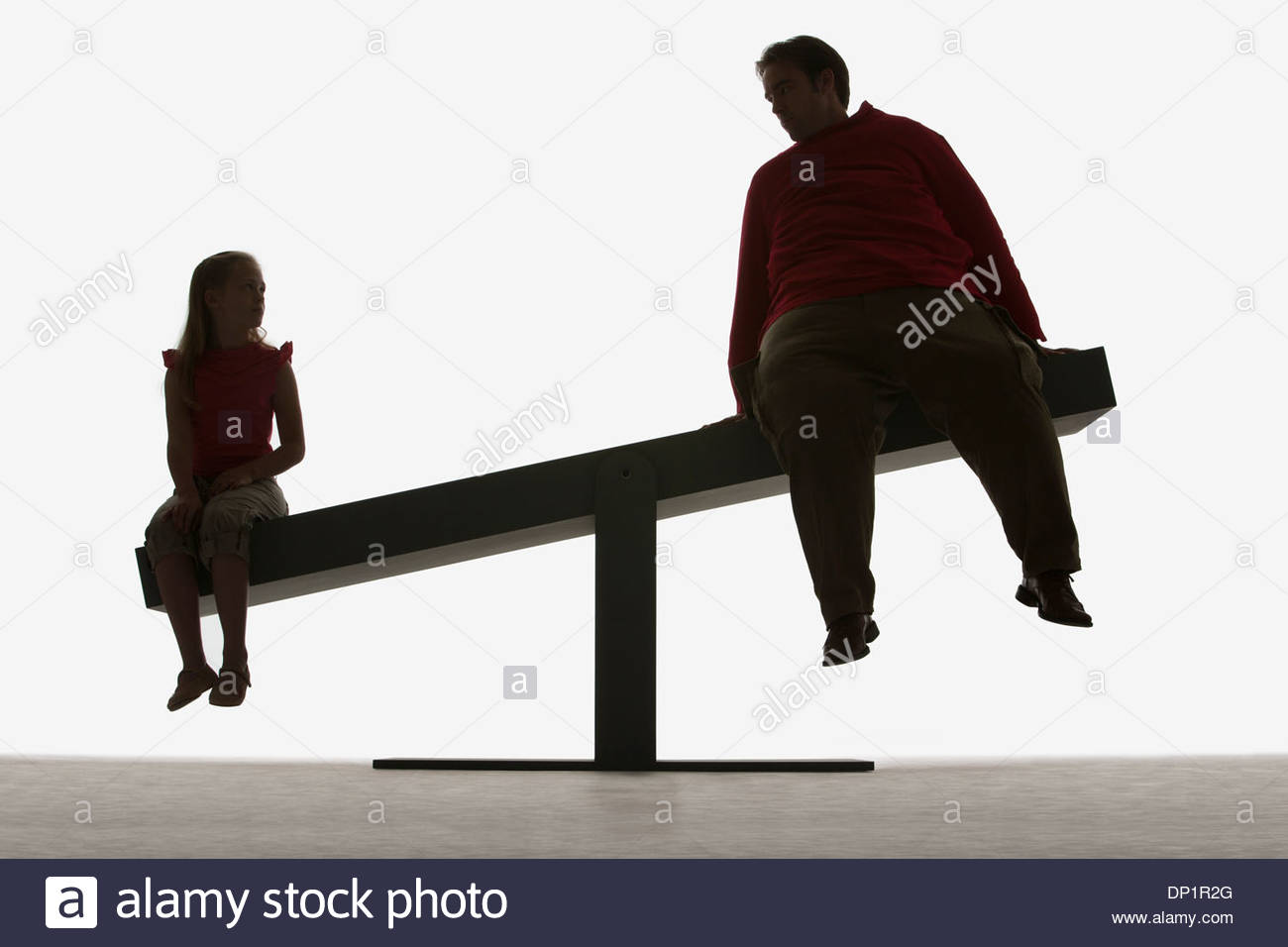 Man and girl sitting on ends of a plank - Stock Image