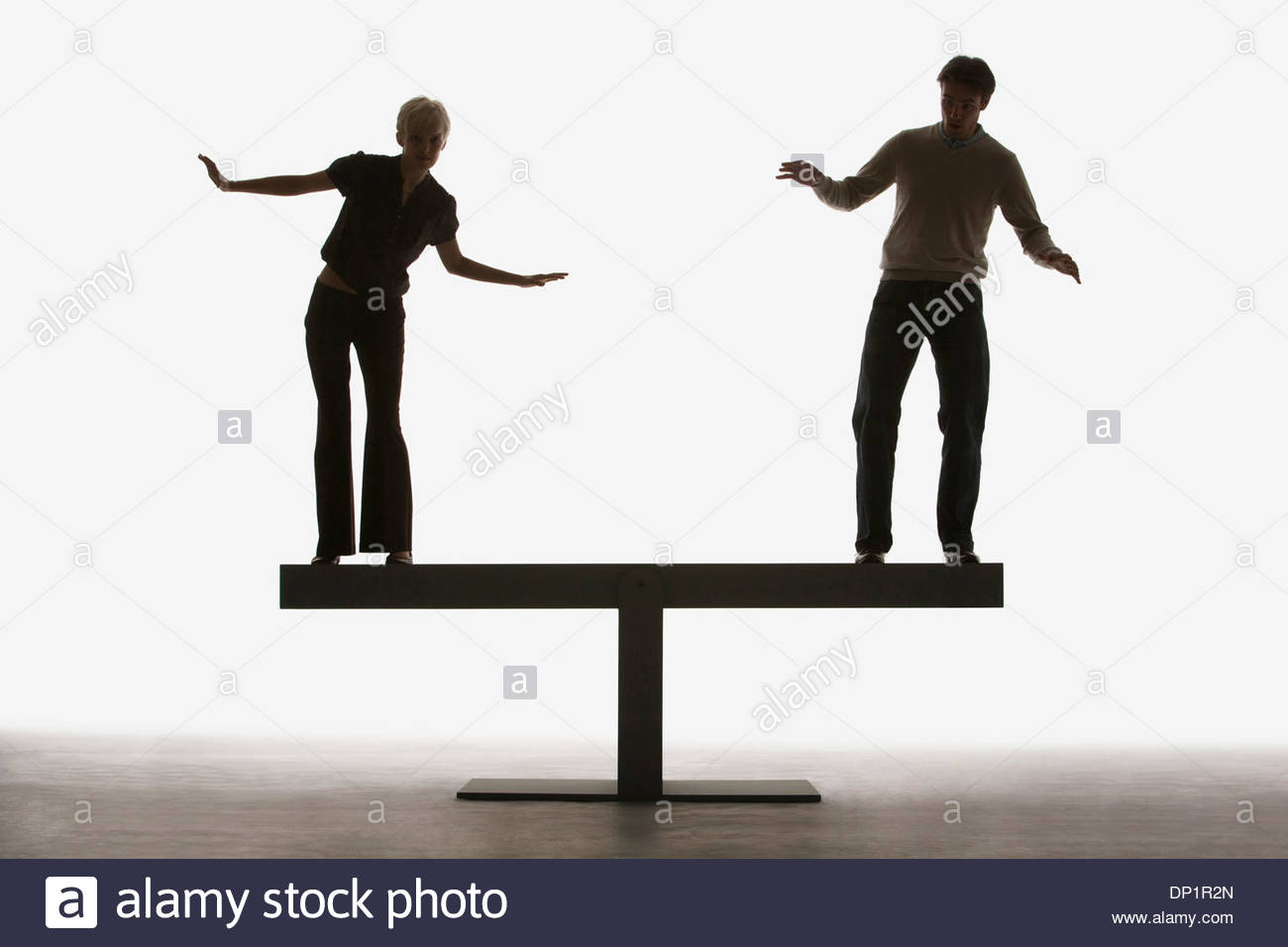 Two people balancing on top of a plank - Stock Image