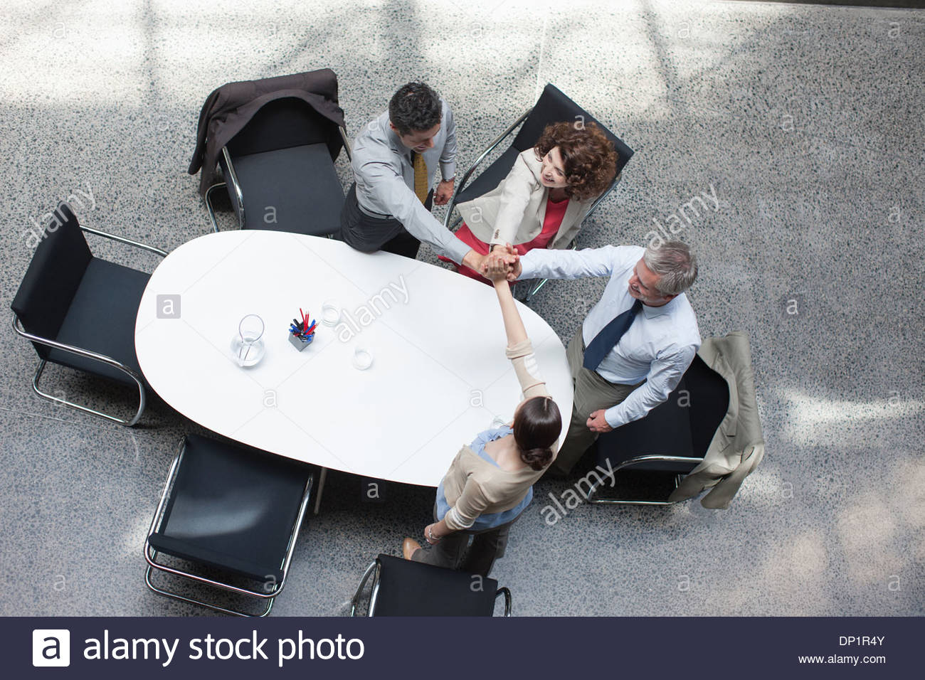 Directly above business people stacking hands at conference table - Stock Image
