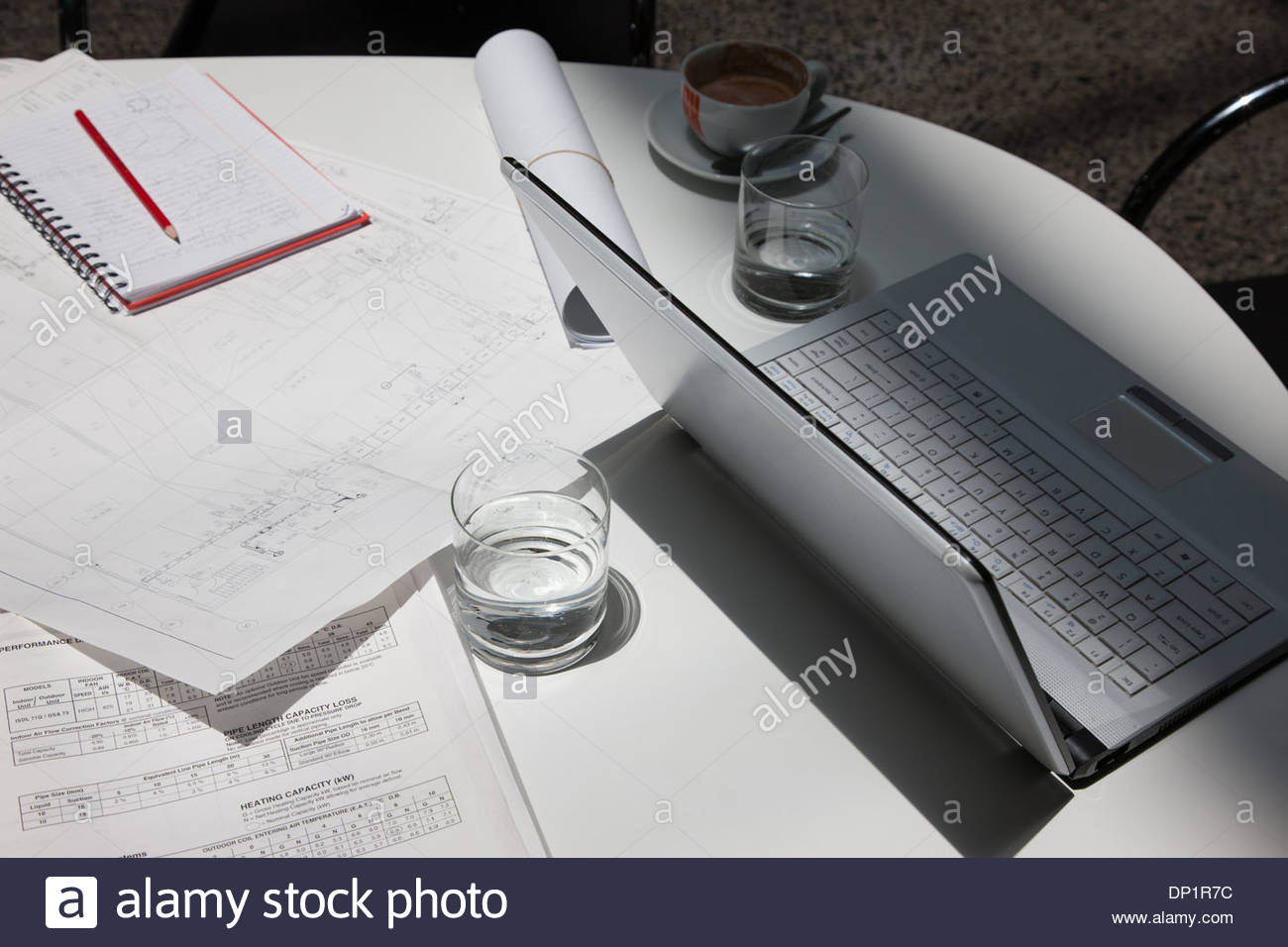 Directly above paperwork, coffee, laptops and notebooks on conference table - Stock Image