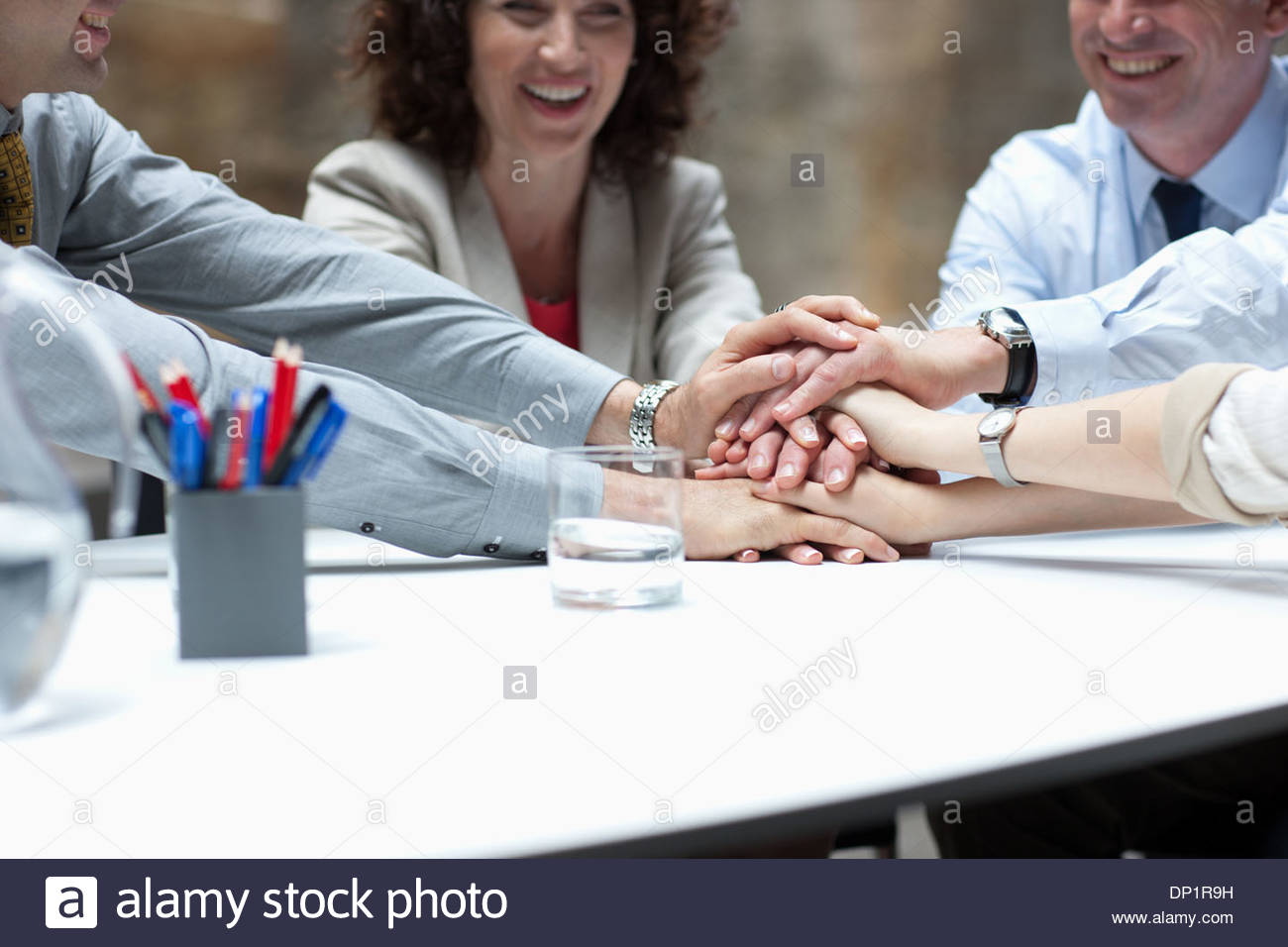 Business people stacking hands in meeting - Stock Image