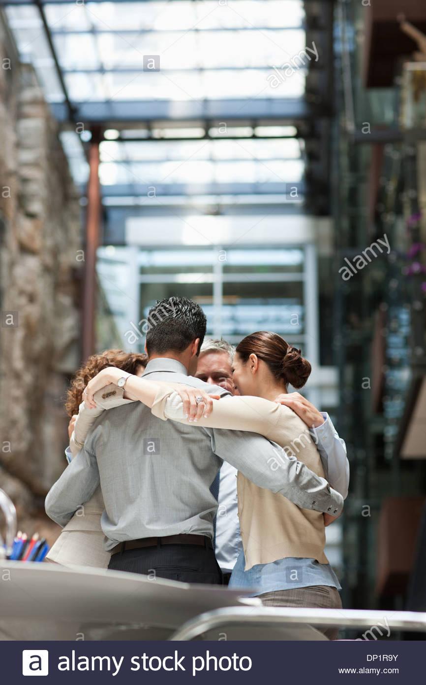 Business people hugging - Stock Image