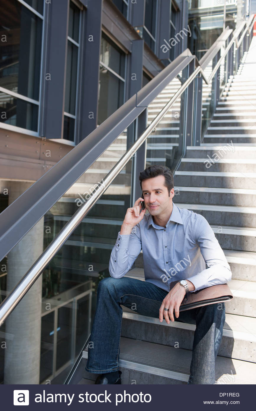 Man sitting on stairs and talking on cell phone - Stock Image