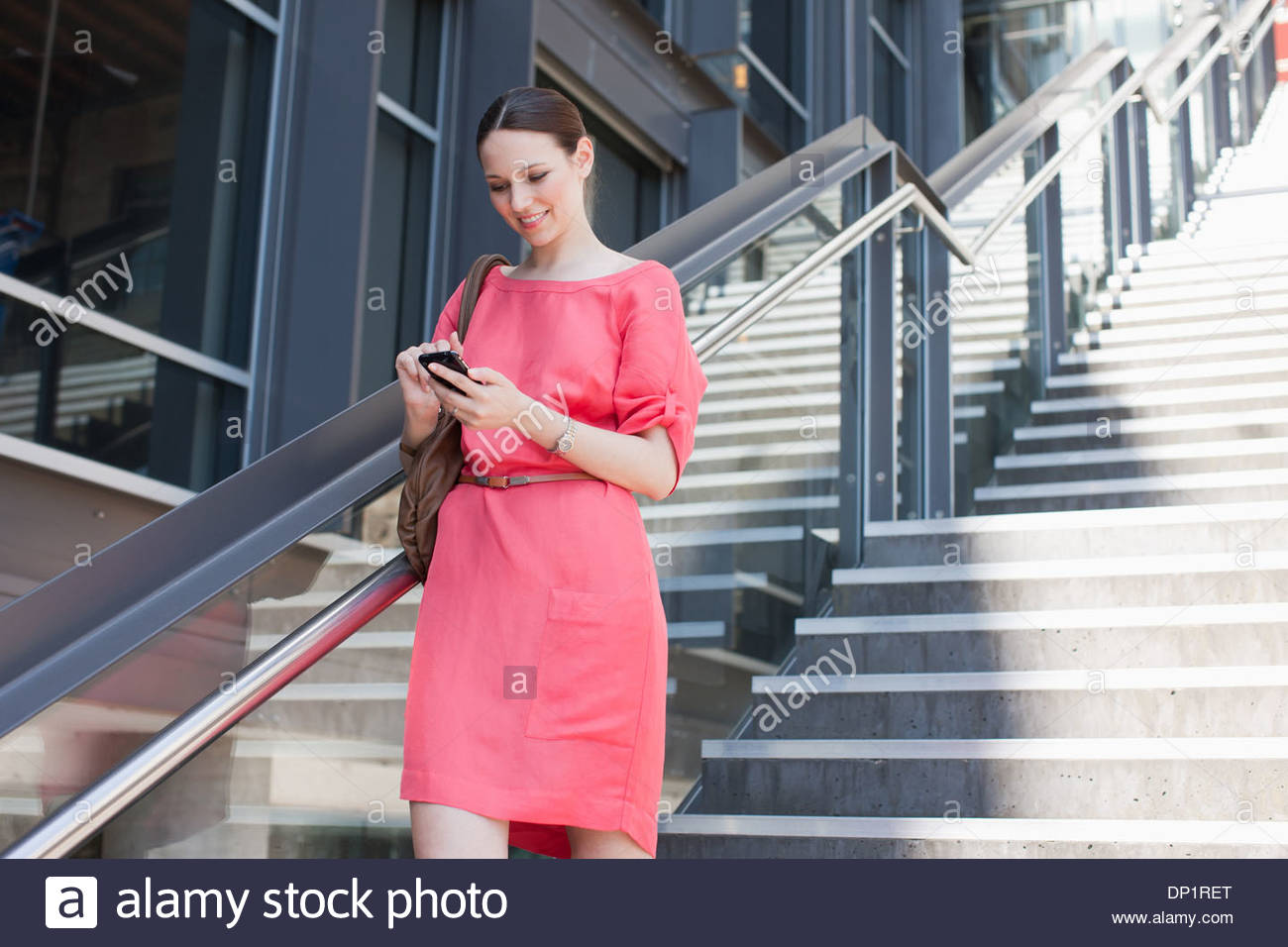 Woman using cell phone on sunny stairs - Stock Image