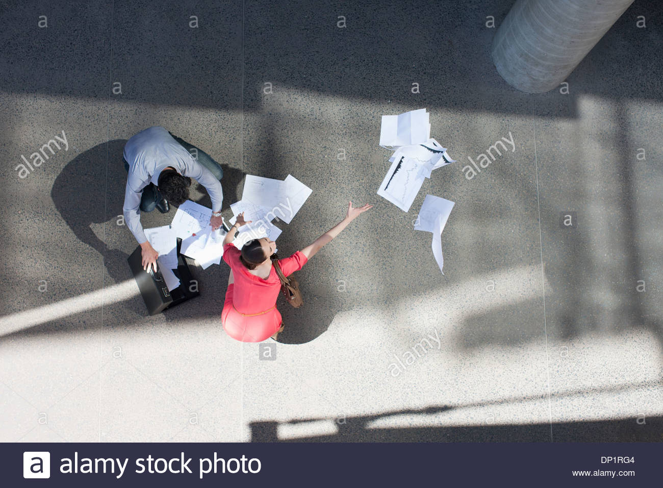 Businessman and businesswoman collect  paper - Stock Image