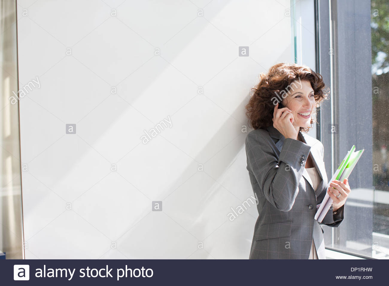 Businesswoman talking on cell phone by window - Stock Image