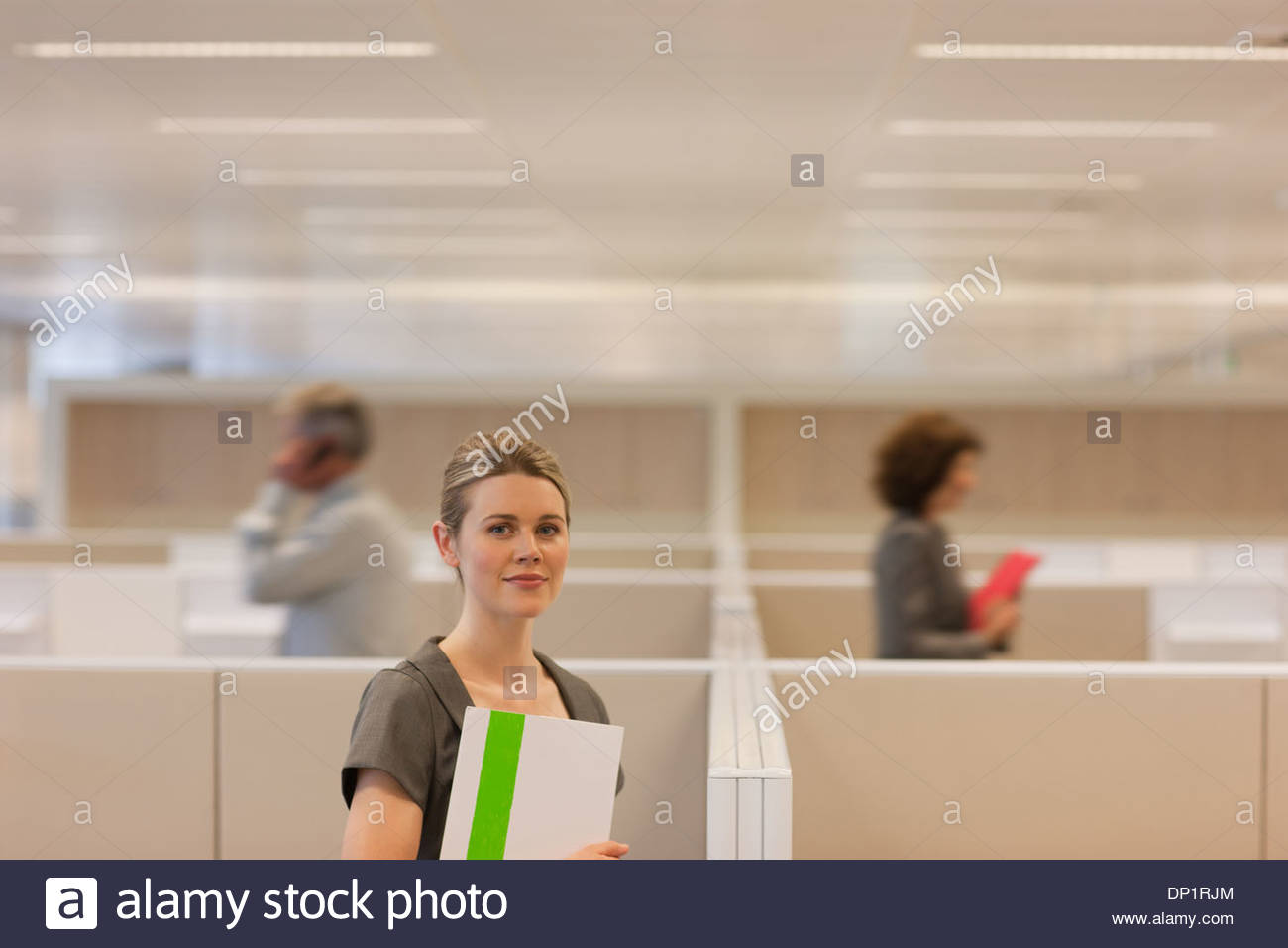 Businesswoman standing in office cubicle - Stock Image