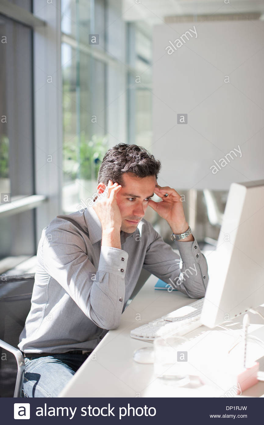 Businessman looking at computer with head in hands - Stock Image