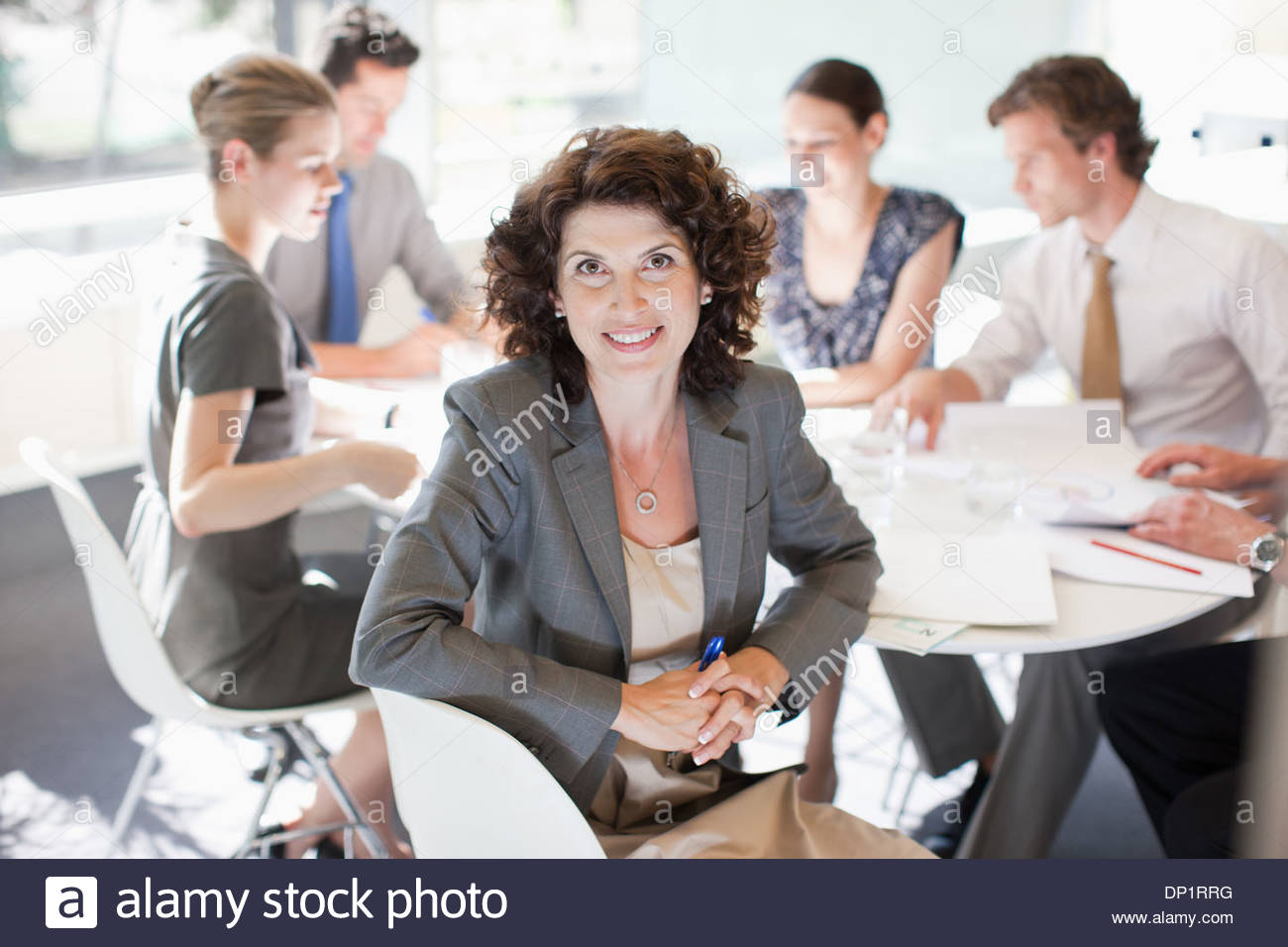 Businesswoman and co-workers meeting at conference table - Stock Image
