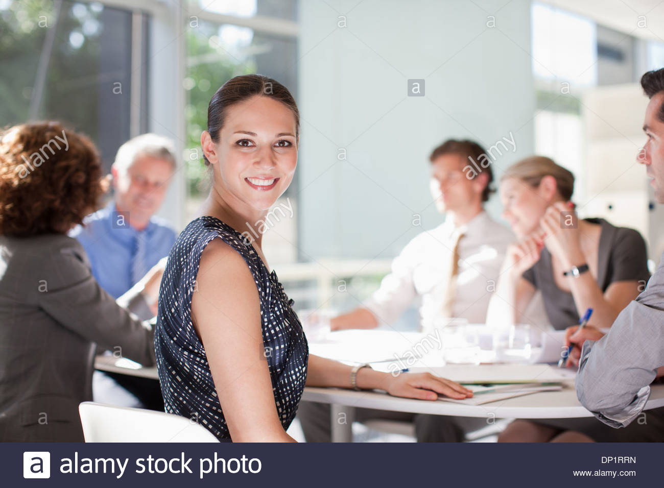 Businesswoman with co-workers meeting at conference table - Stock Image