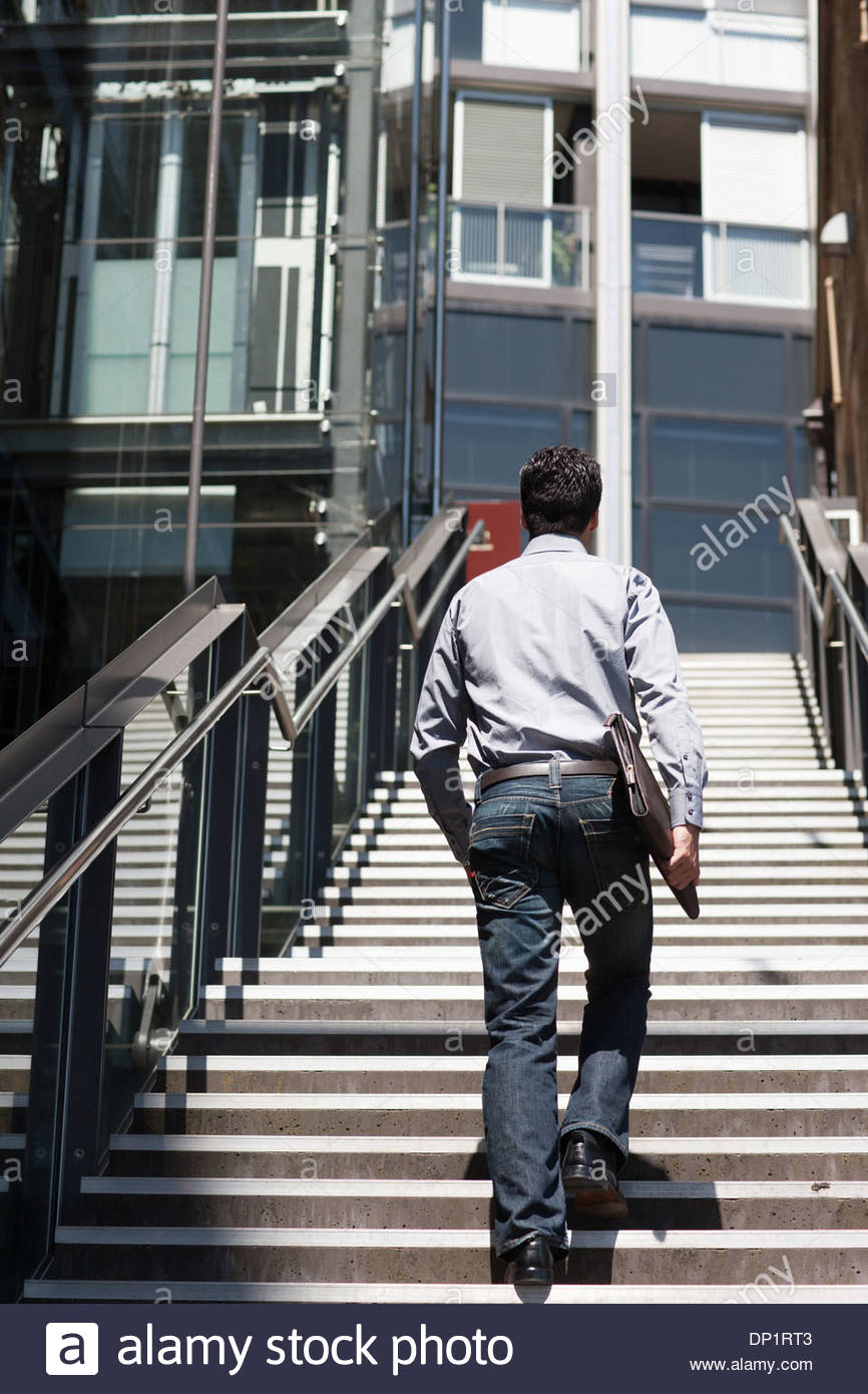 Businessman walking up stairway, rear view - Stock Image