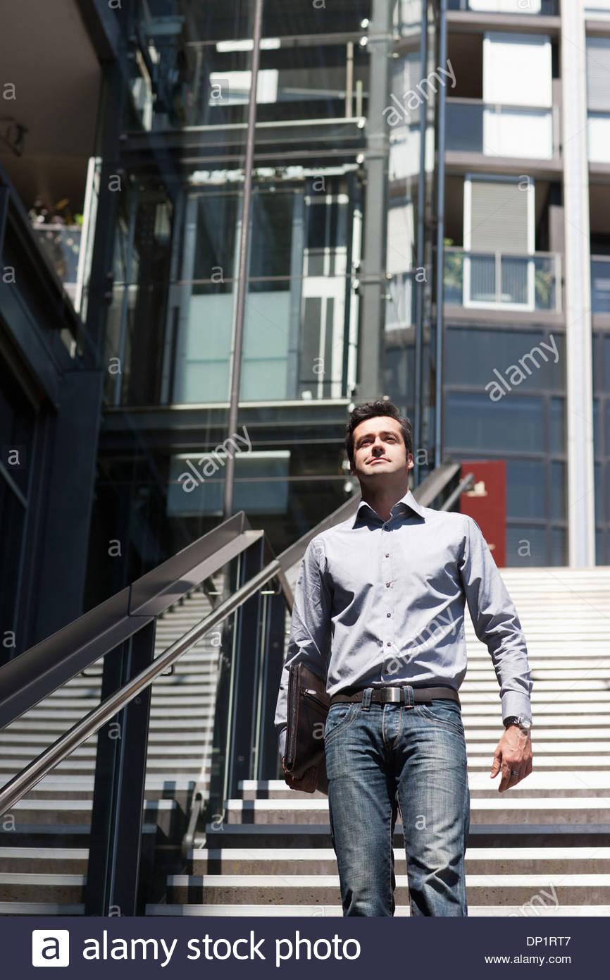 Businessman walking down stairway - Stock Image