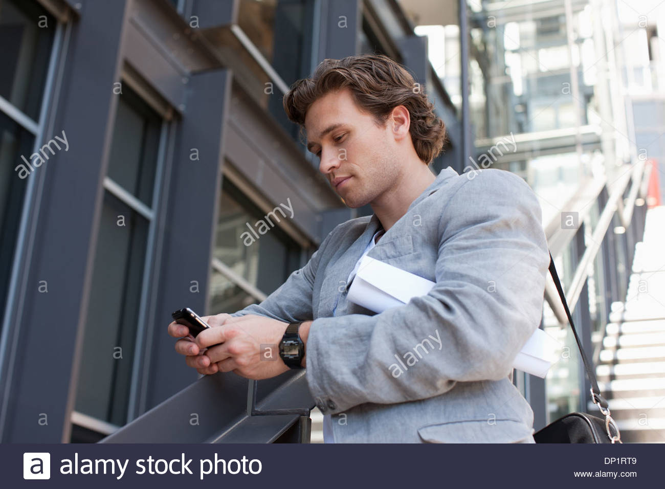 Man using cell phone on stairs - Stock Image