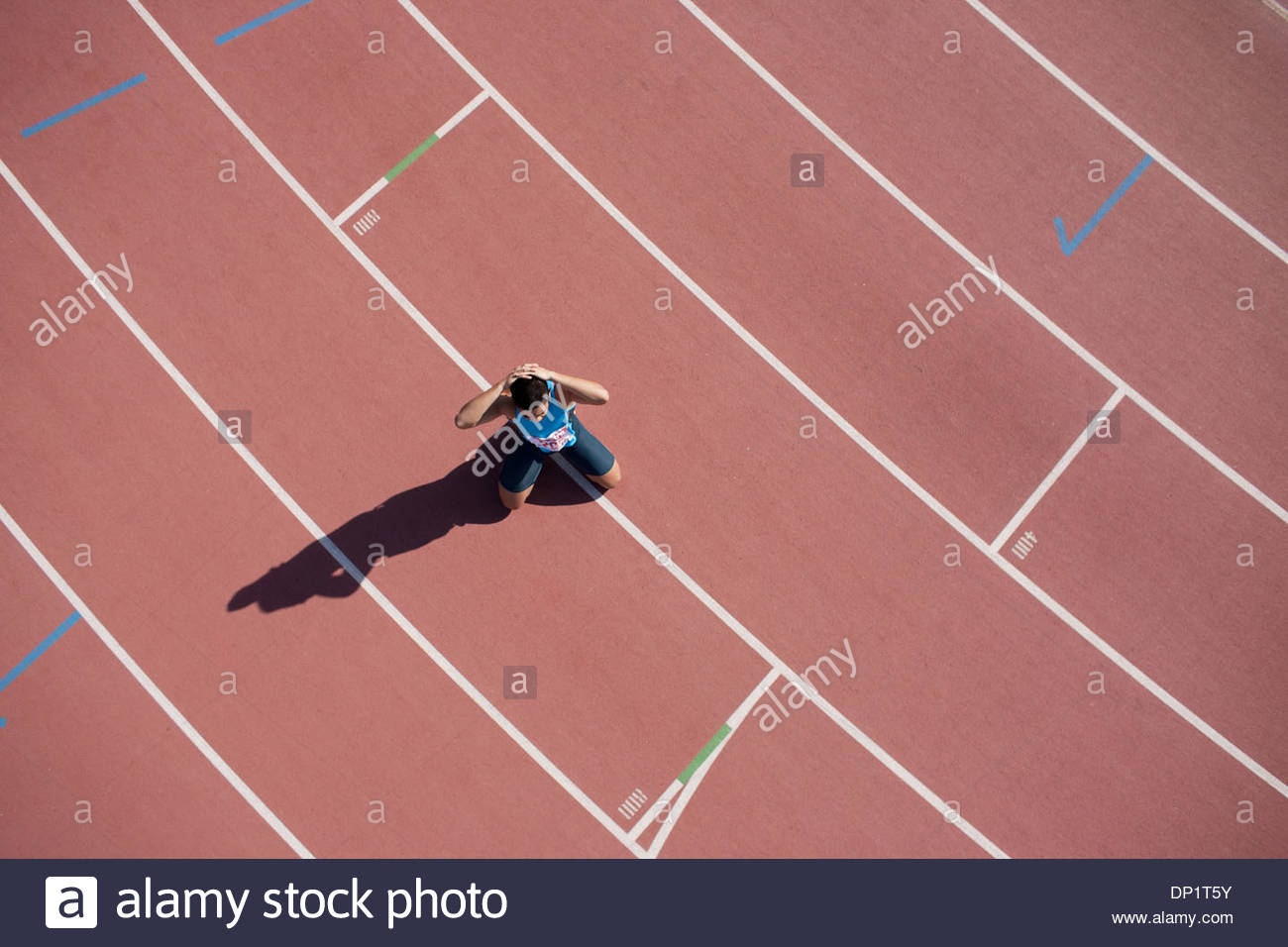 Disappointed runner kneeling on track - Stock Image