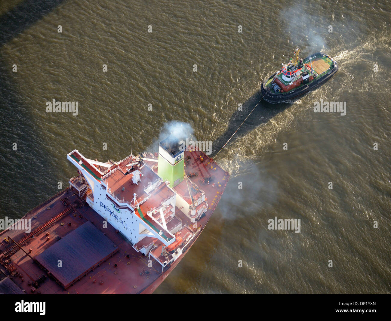 Bugsier 9 tug boat towing the Bergebulk Arctic from the harbor, Hamburg, Germany - Stock Image