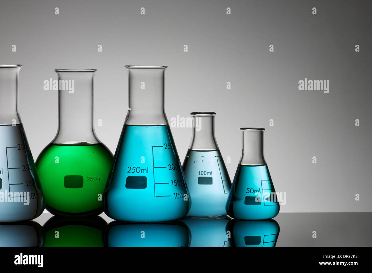 laboratory flasks with brightly colored liquid inside - Stock Image