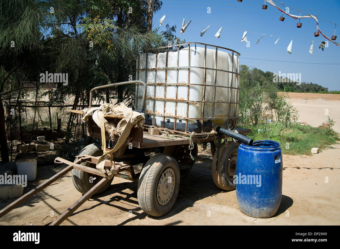 A family without running water has to use water tanks. - Stock Image