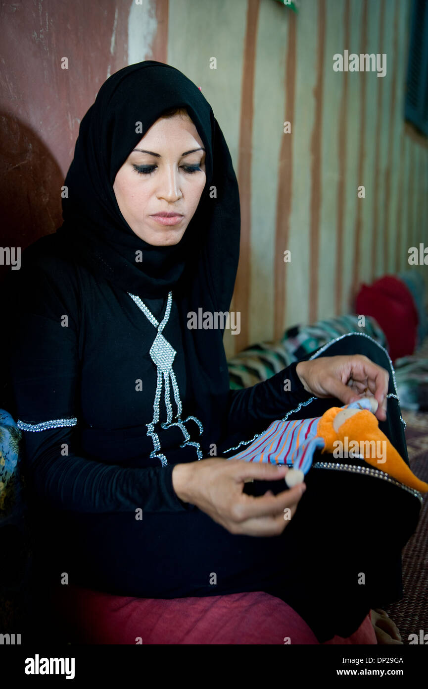 Bilbeis, Egypt: Young Egyptian woman working as a seamstress at home for Sekem company in order to have a little income - Stock Image