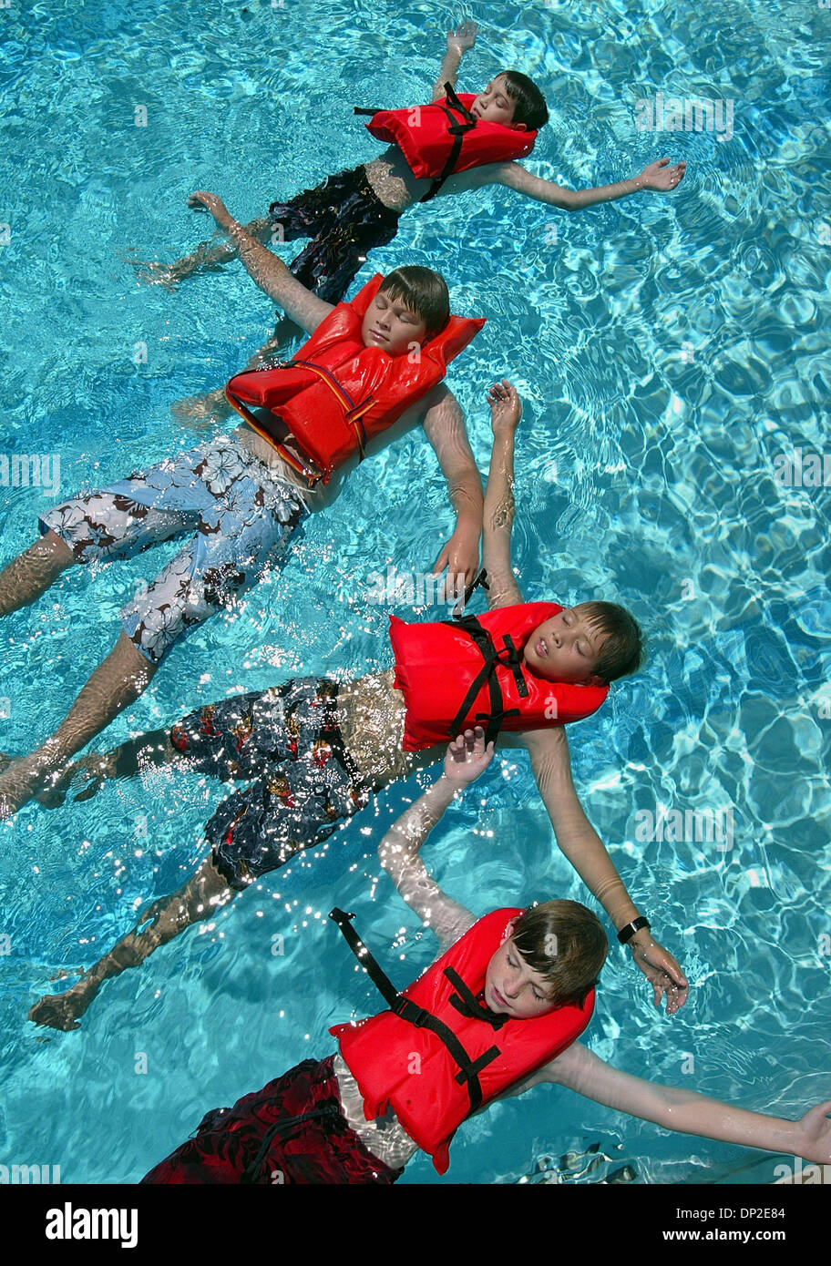 May 31, 2006; Delray Beach, FL, USA; Cub Scouts from Pack 233, (bottom to top) Cameron Keller, 10, Christopher Gibb, 10, Anthony Zaleski, 10 and Pierce Palma, 10, float on their backs wearing personal flotation devises while taking a test for their aquanaut badge at Aquacrest Pool, Wednesday afternoon.  Aquacrest pool manager Joe McNeeley administered the test which included water  - Stock Image