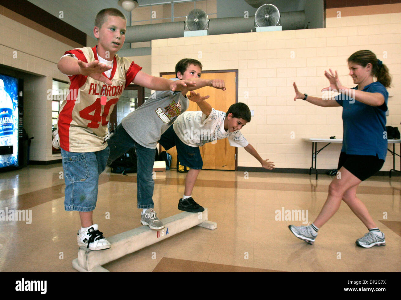 Jun 02, 2006; Fallbrook, CA, USA; Fitness Frenzy owner HEIDI RANSOM (who is running the kid's fitness program here), at right, directs kids on the balance beam. LtoR: BOSTON MENOSSI, AERIS SOUFLIS, and MARTIN ESCOBEDO. Mandatory Credit: Photo by Charlie Neuman/SDU-T/ZUMA Press. (©) Copyright 2006 by SDU-T - Stock Image